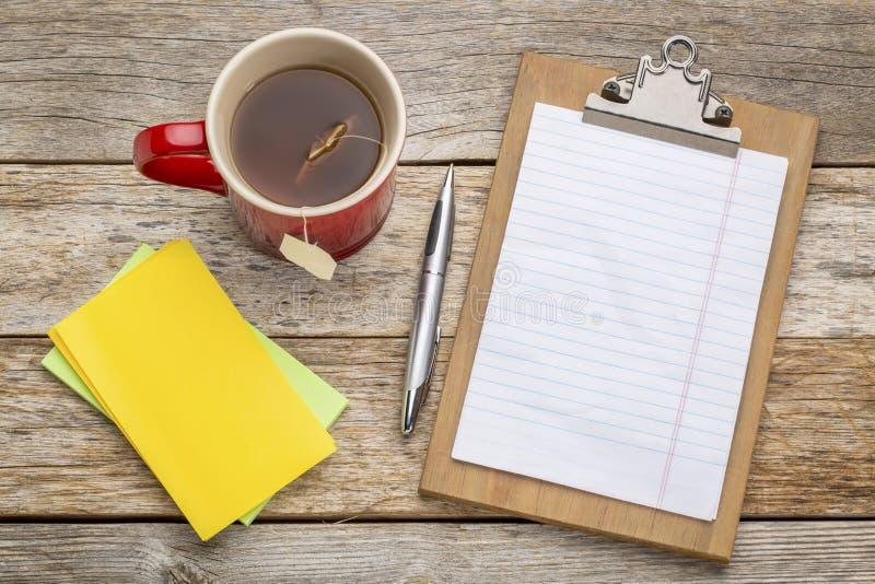 在剪贴板和茶的白纸 免版税库存照片