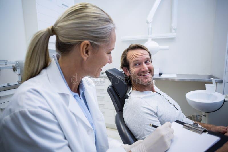 在剪贴板的女性牙医文字,当互动与男性患者时 免版税库存照片