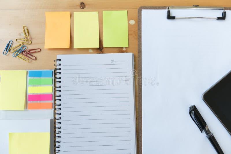 在剪贴板的白纸有片剂的,笔,笔记本,稠粘的笔记 库存图片