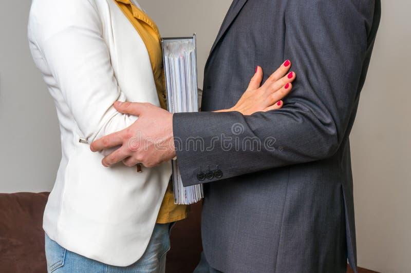 在办公室供以人员感人的妇女` s手肘-性骚扰 免版税库存图片