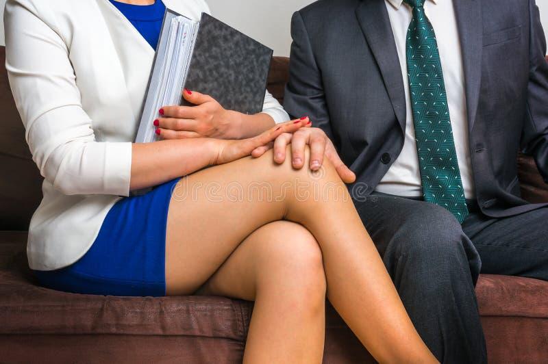 在办公室供以人员感人的妇女` s膝盖-性骚扰 免版税库存图片