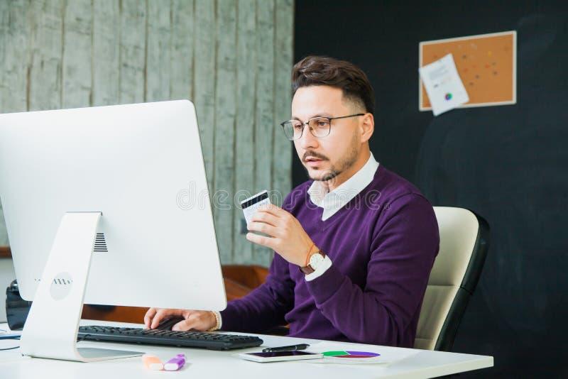 在办公室信用卡网上商务的年轻商人 库存图片