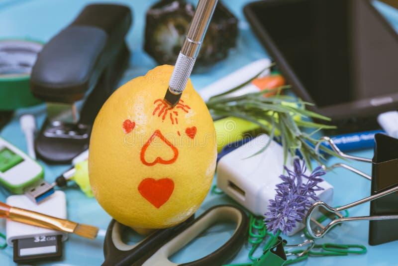 在办公室刀子被插入作为隐喻的柠檬画的丘比特画象 库存图片