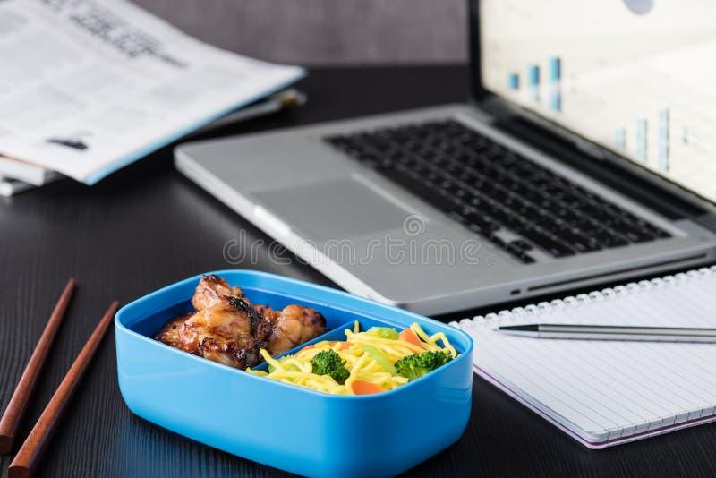 在办公室午餐期间的家庭厨师bento箱子与计算机膝上型计算机 免版税库存照片