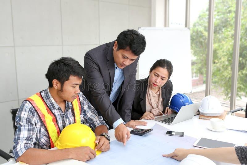 在办公室合作工程师工作会室 队工作者谈建筑计划 电工木匠或技术 免版税库存照片