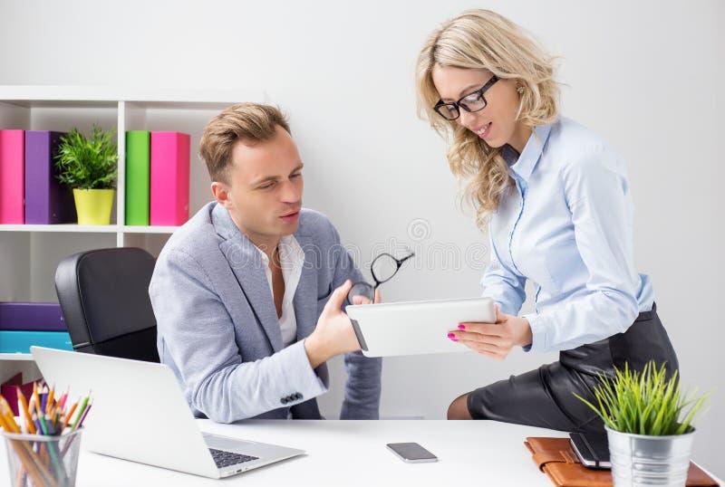 在办公室和看片剂计算机的两个同事 免版税图库摄影