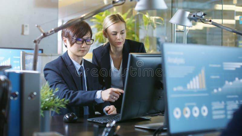 在办公室商人坐在他的与他的上司的书桌谈话, 免版税库存图片