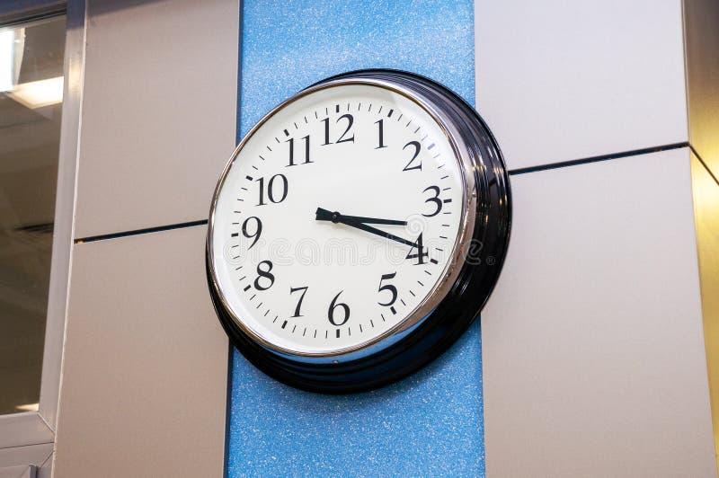 在办公室墙壁上的圆的时钟 库存图片