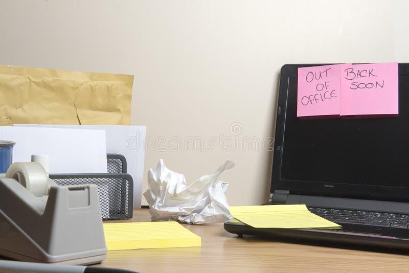 在办公室外面,后面消息在杂乱办公桌很快离开 免版税库存照片