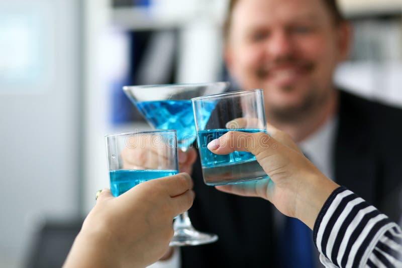 在办公室庆祝与蓝色酒精液体的同事重要事项在玻璃 库存照片