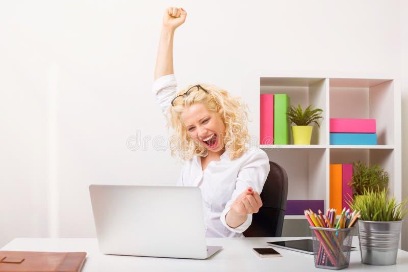 在办公室庆祝她的成功的Beuatifull妇女 库存图片