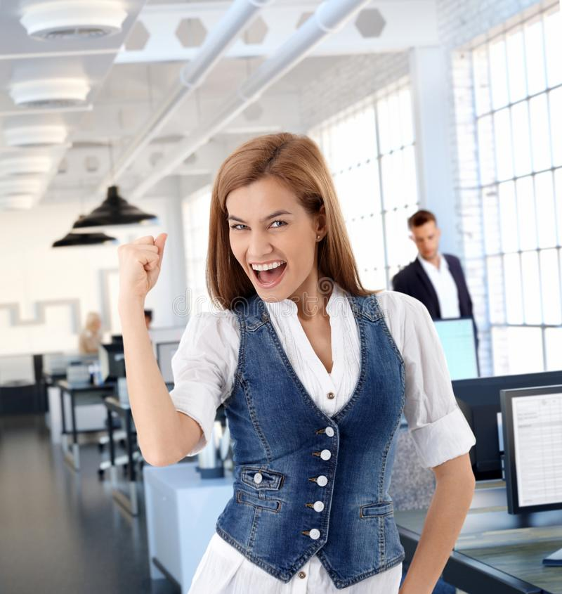 在办公室庆祝成功的激动的妇女 库存照片