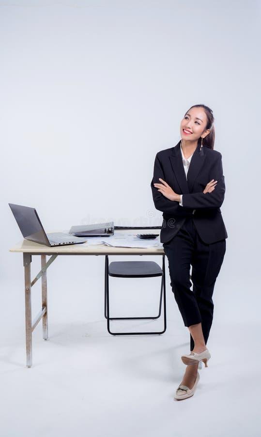 在办公室微笑对照相机的确信的女实业家 库存图片