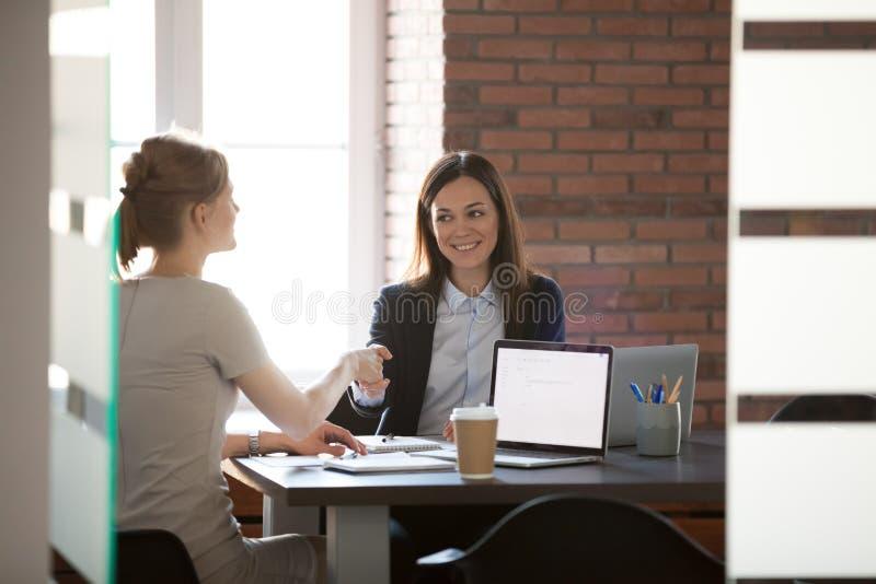在办公室感谢的微笑的女实业家同事握手 库存照片