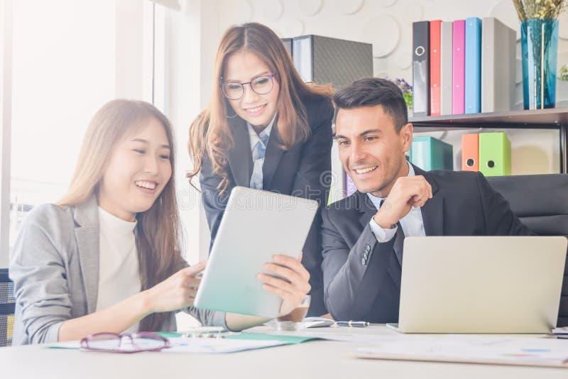 在办公室月会期间,欢呼的愉快的商人,与胳膊的愉快的企业队提高了坐在办公室 图库摄影