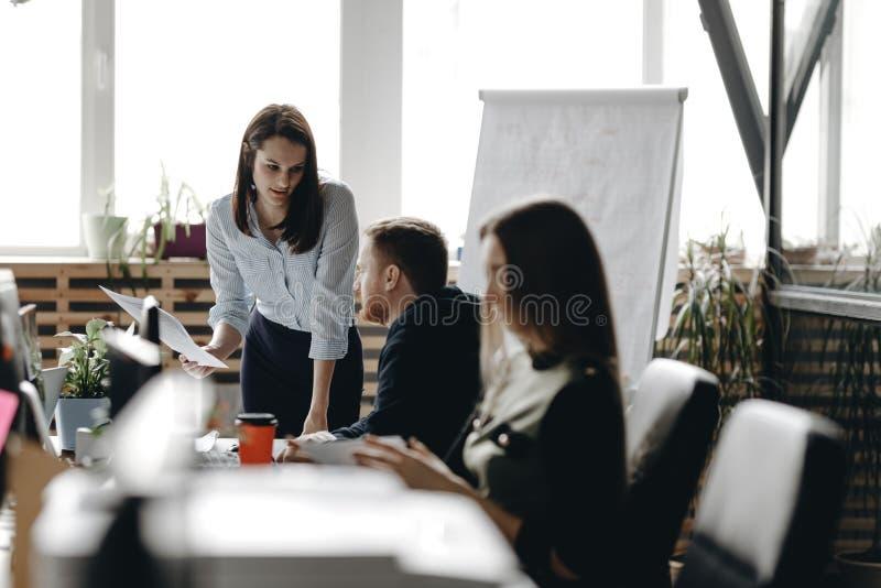 在办公室样式衣裳打扮的年轻深色的女孩坐在有同事的书桌并且保留笔记本 库存照片