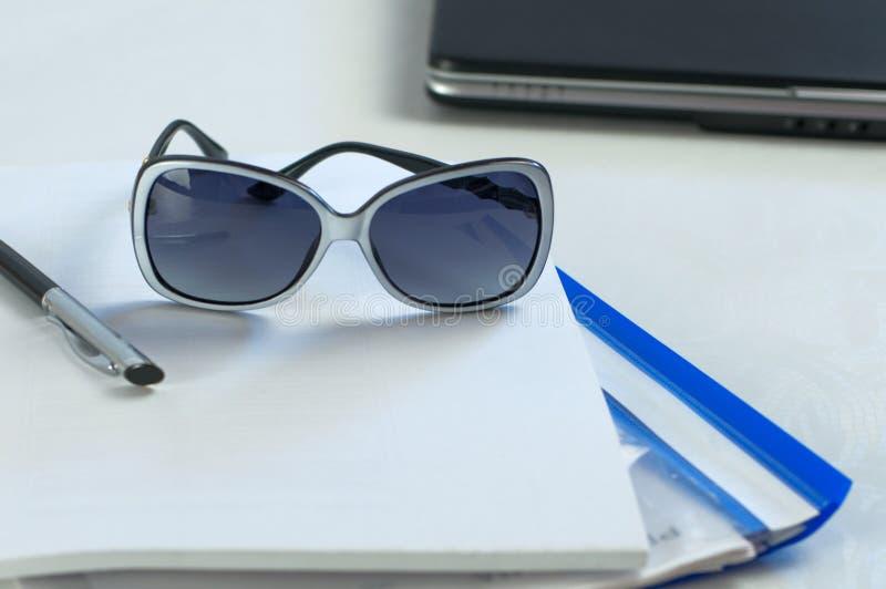在办公室桌上的太阳镜谎言 库存图片