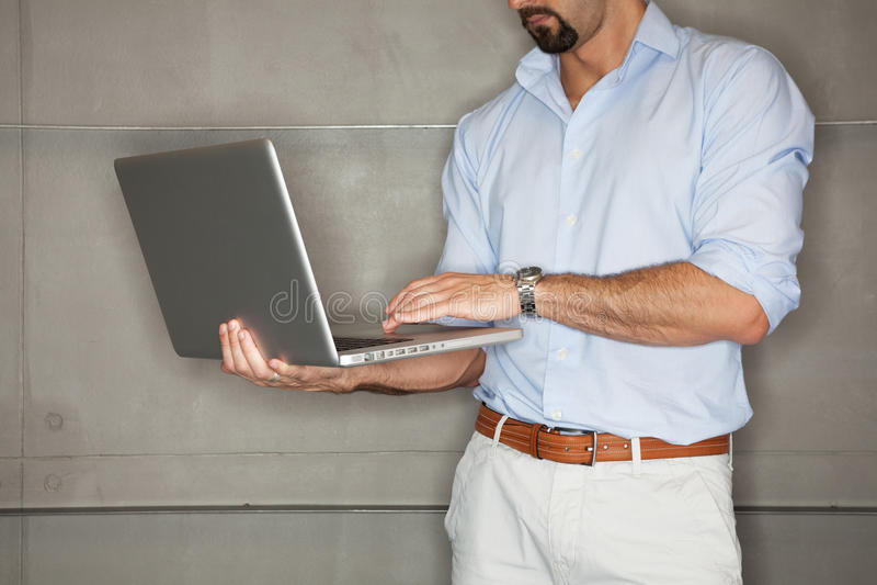 在办公室检查他的在膝上型计算机的人介绍。 免版税图库摄影