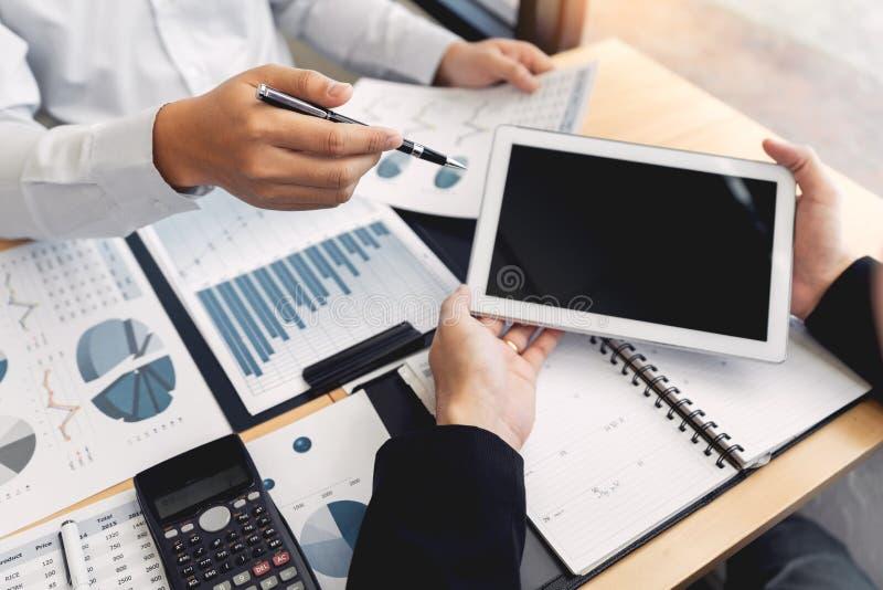 在办公室概念,使用触感衰减器数字片剂的年轻商人谈论在市场或stoc上的情况 免版税库存图片