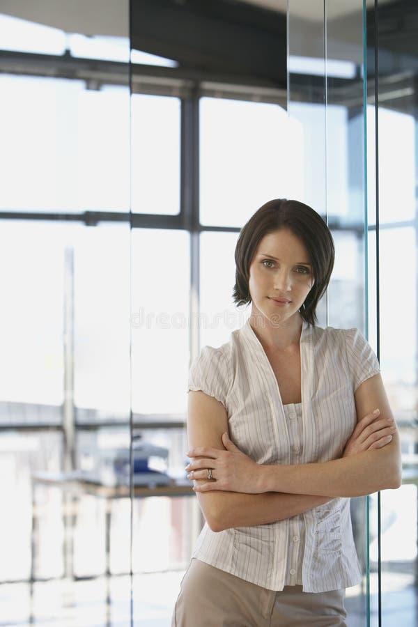 在办公室横渡的女实业家常设胳膊 免版税图库摄影