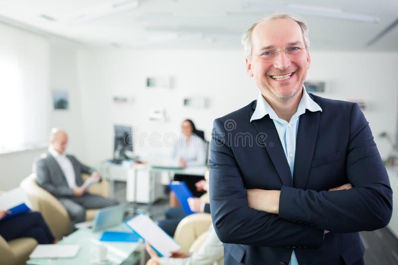 在办公室横渡的微笑的资深商人站立的胳膊 库存图片