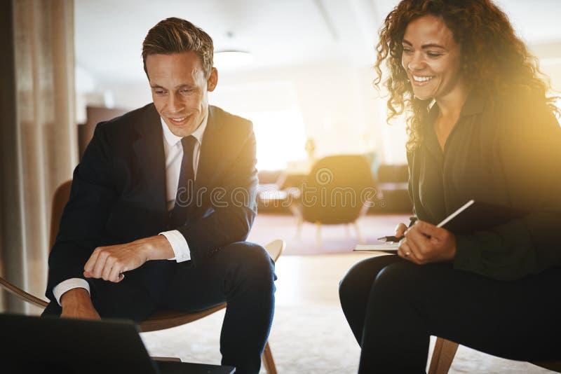 在办公室的两微笑的不同的买卖人 图库摄影