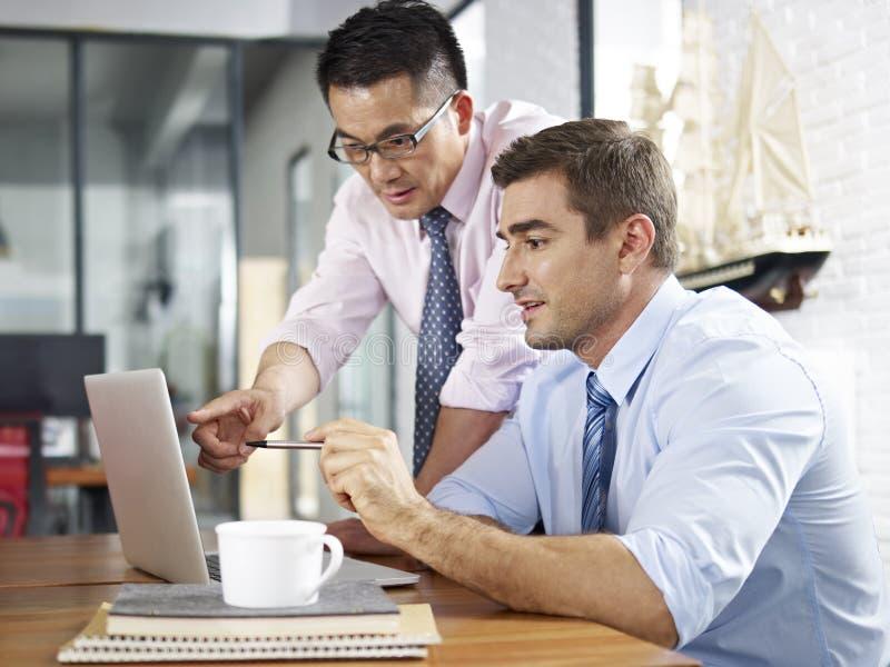 在办公室的亚洲和白种人商人 免版税库存照片