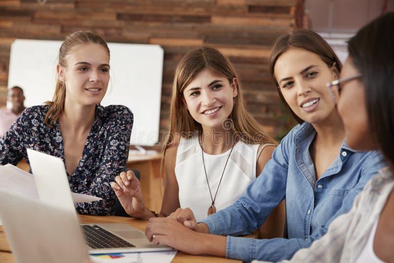 在办公室的四个女性同事 图库摄影
