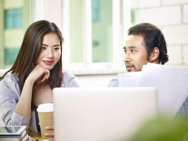 在办公室的年轻亚裔工友使用膝上型计算机co 库存图片