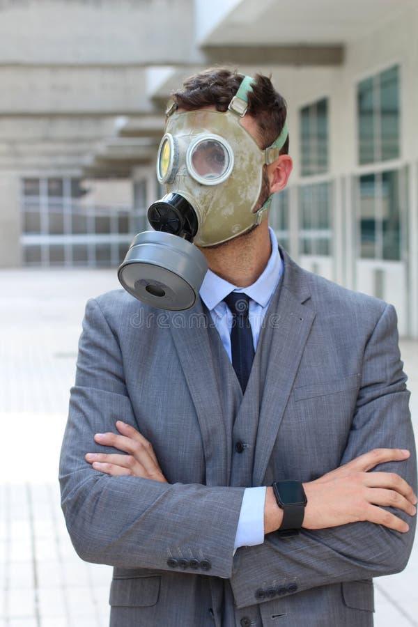 在办公室空间的商人佩带的防毒面具 库存图片