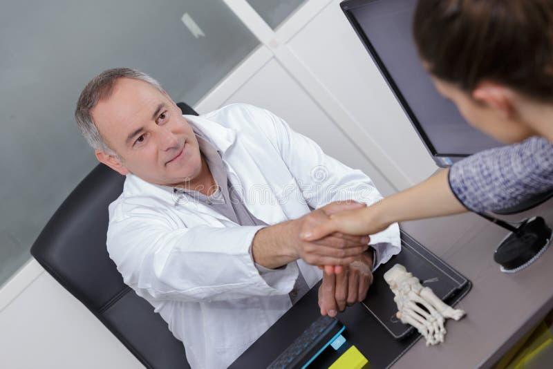 在办公室篡改与患者的握手在医院 免版税图库摄影