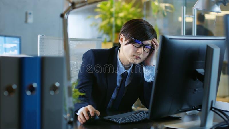 在办公室绝望商人在个人的桌面上工作 库存图片