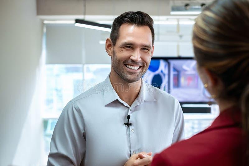 在办公室谈话和微笑在公司采访中的商人 免版税库存照片