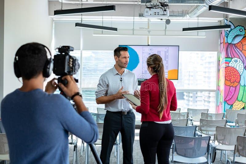 在办公室谈话和微笑在公司采访中的商人 库存图片