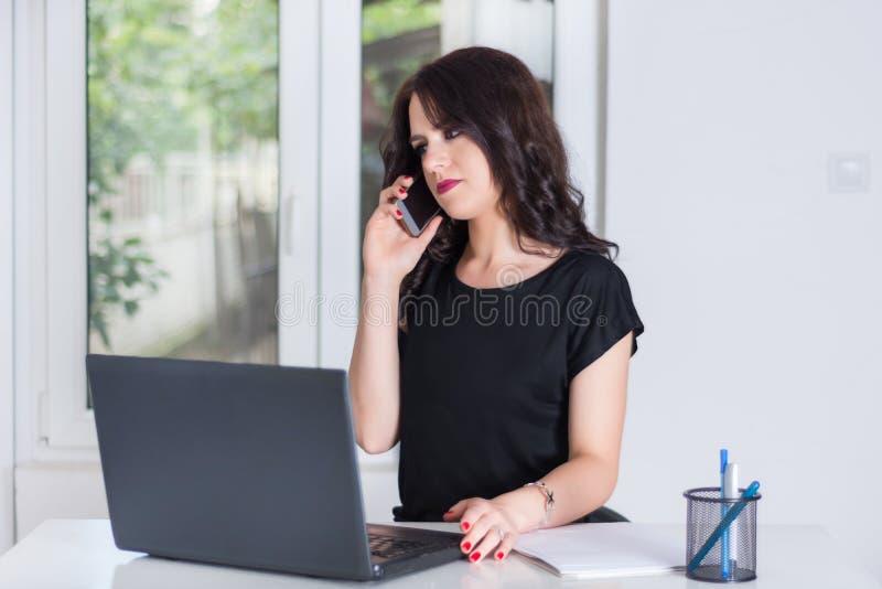 在办公室谈话在手机和研究膝上型计算机的逗人喜爱的女商人 库存照片
