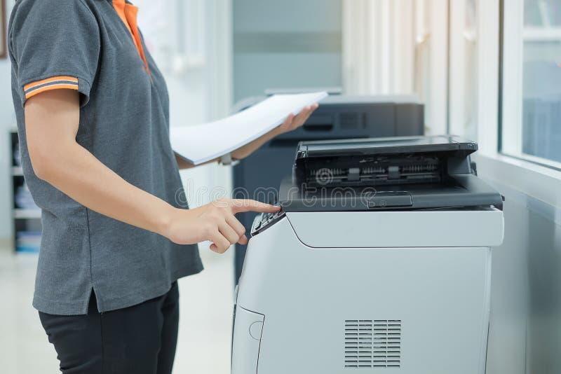在办公室递放文件纸入打印机扫描器或激光拷贝机器 免版税库存照片