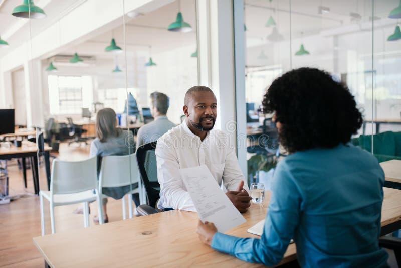 在办公室采访中的微笑的求职者回答的问题 免版税库存照片