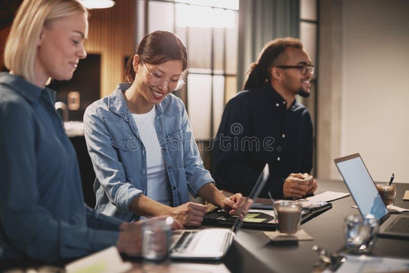 在办公室里微笑和交谈的不同商人 库存图片