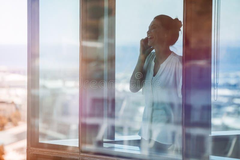 在办公室里面的微笑的女实业家和谈话在手机 免版税库存照片