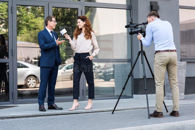 在办公室附近的专业摄影师和新闻记者采访的商人 库存照片