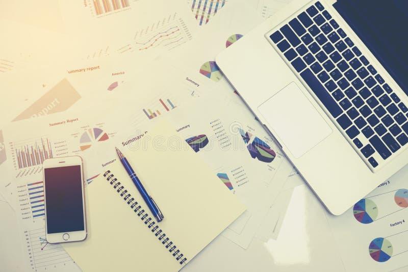 在办公室财政桌上的商业文件与巧妙的电话和数字式片剂和的图表 免版税库存照片