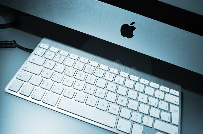 在办公桌上的Mac苹果电脑在工作地点 免版税库存图片