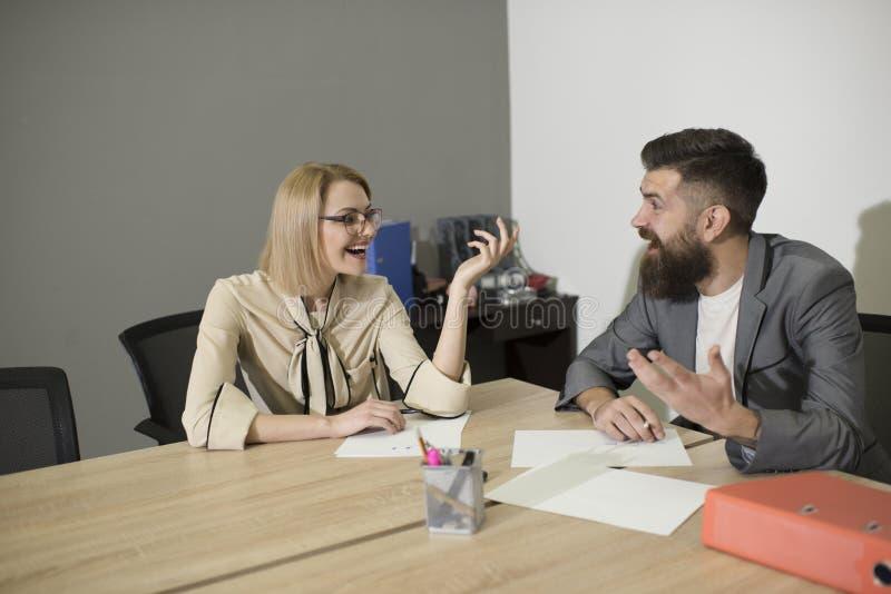 在办公桌的同事愉快的微笑 微笑在业务会议上的同事在办公室、通信和合作 库存照片