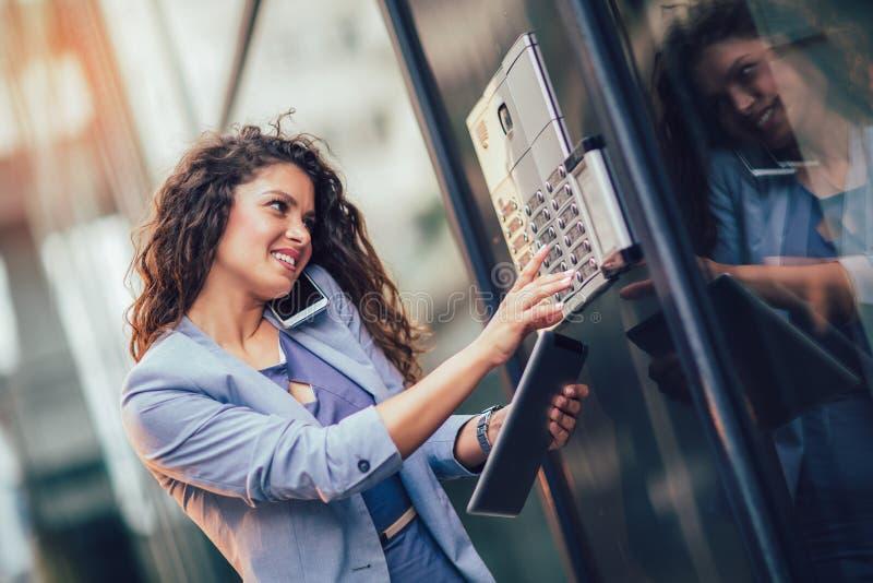 在办公楼之外的年轻愉快的女实业家,进入大厦 库存照片