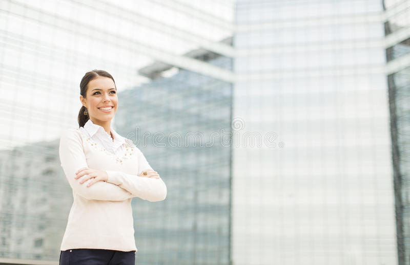 在办公楼前面的女商人 免版税库存照片