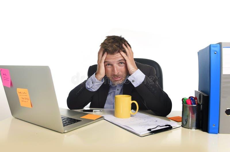 在办公计算机书桌的被用尽的商人痛苦重音淹没了疲乏 库存图片