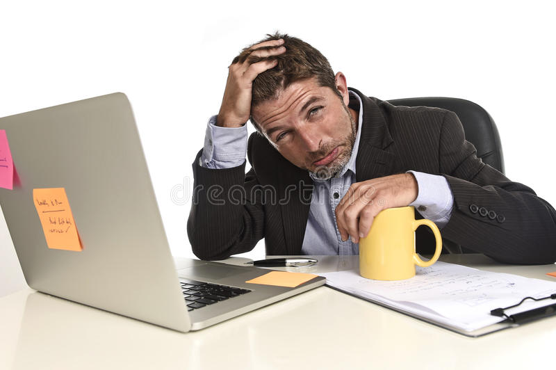 在办公计算机书桌的被用尽的商人痛苦重音淹没了疲乏 图库摄影