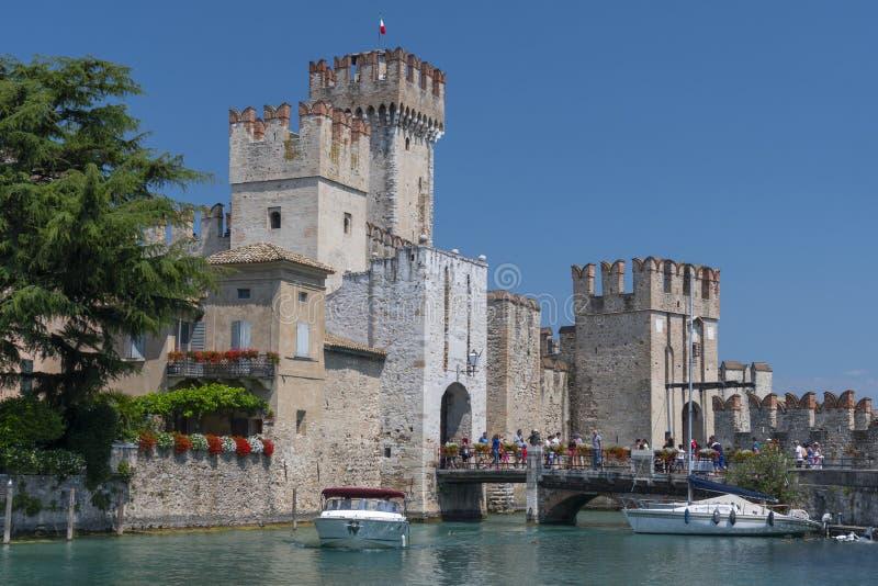 在加尔达湖的小船和中世纪Scaliger城堡在西尔苗内,意大利镇  免版税图库摄影