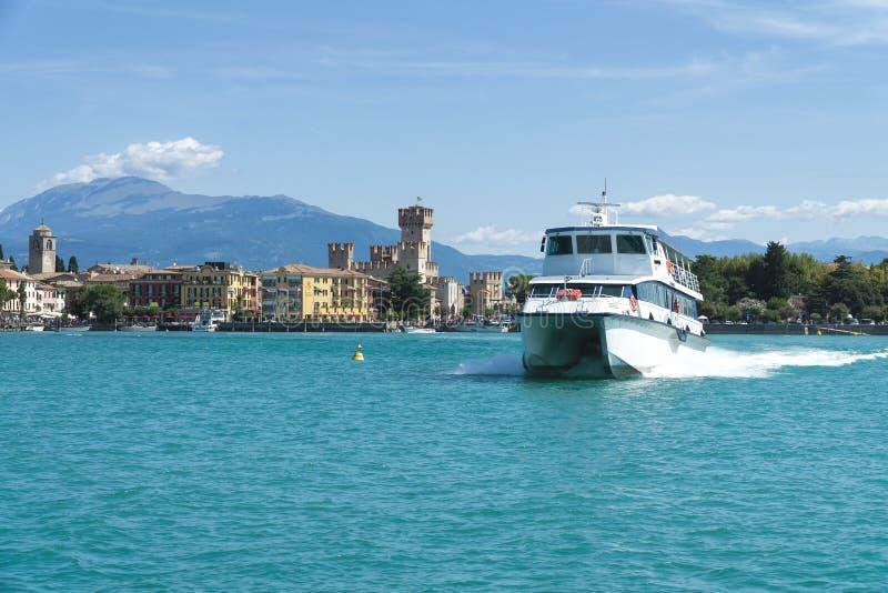 在加尔达湖的旅游船 西尔苗内和Caligero城堡全景  免版税库存照片