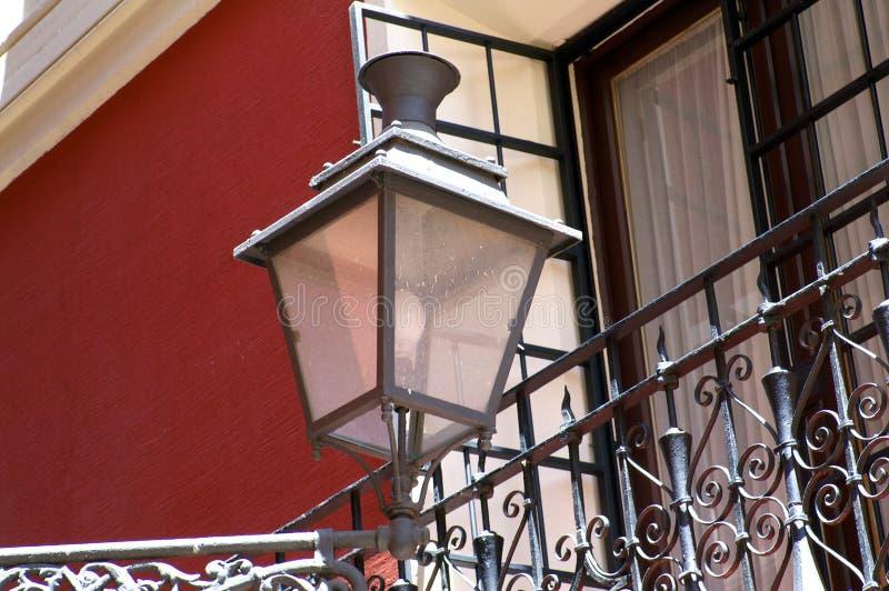 在加工铁阳台附近的街灯对红色墙壁 免版税库存图片